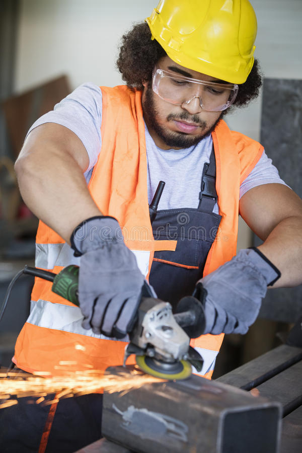 Young manual worker grinding metal in industry.  royalty free stock photos