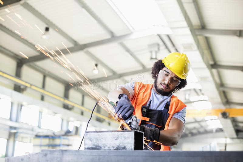 Young manual worker using grinder on metal in factory.  royalty free stock photo