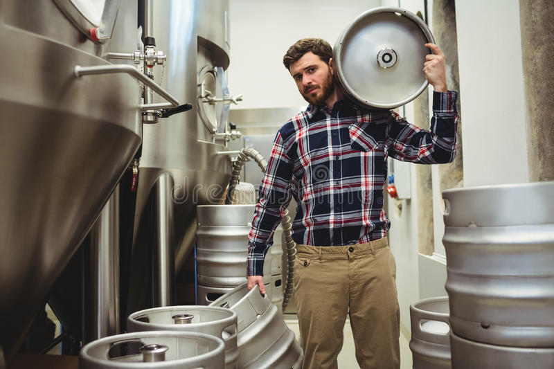 Young manufacturer carrying kegs in brewery. Portrait of young manufacturer carrying kegs in brewery stock photo