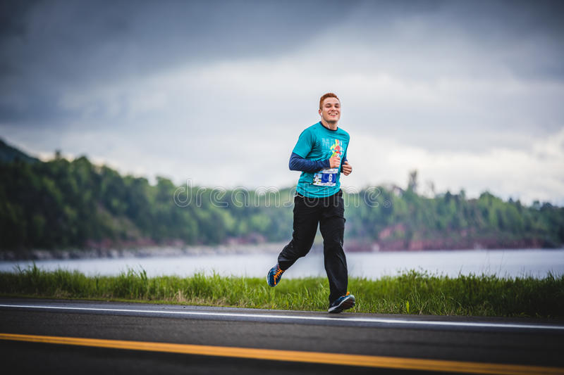 Young Marathoner Alone on the side of the Road and Ocean. CARLETON, CANADA - June 4, 2017. During the 5th Marathon of Carleton in Quebec, Canada. Young stock photos