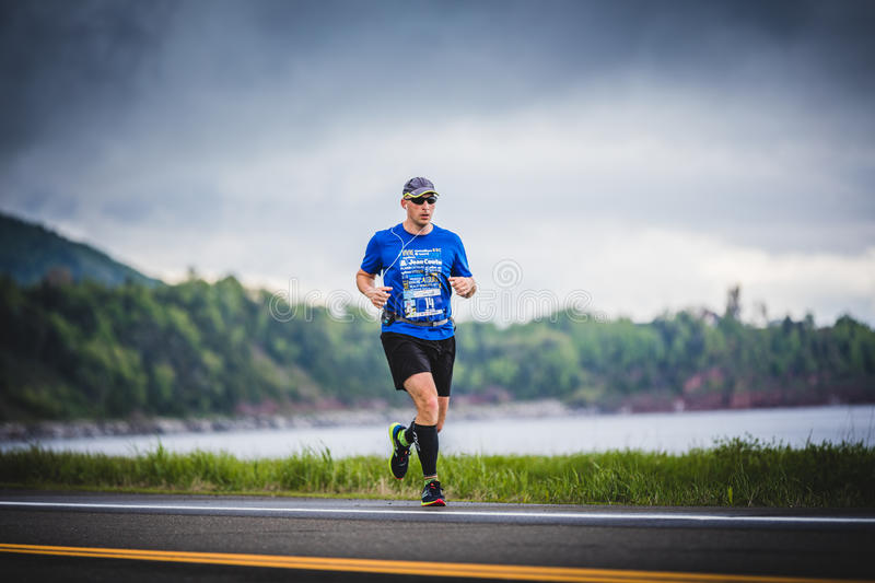 Young Marathoner Alone on the side of the Road and Ocean. CARLETON, CANADA - June 4, 2017. During the 5th Marathon of Carleton in Quebec, Canada. Young stock photo