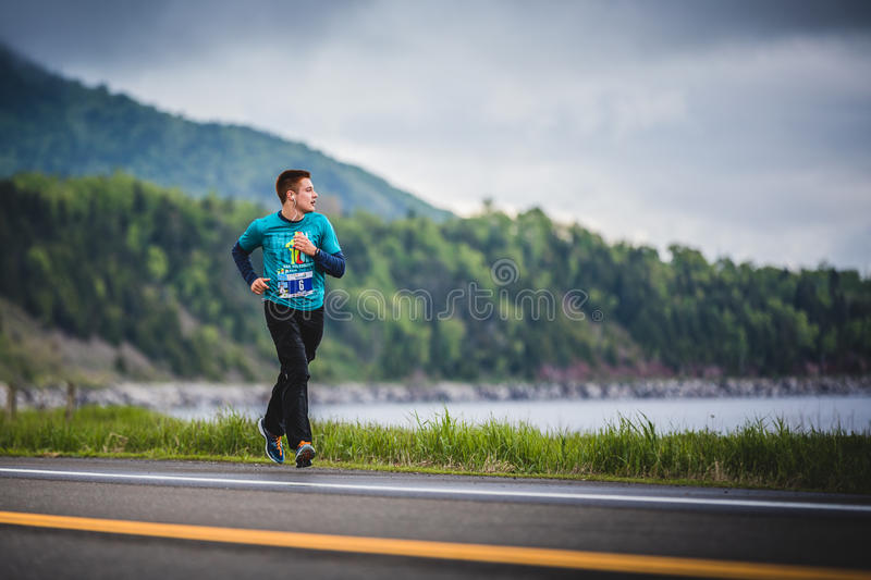 Young Marathoner Alone on the side of the Road and Ocean. CARLETON, CANADA - June 4, 2017. During the 5th Marathon of Carleton in Quebec, Canada. Young stock photography