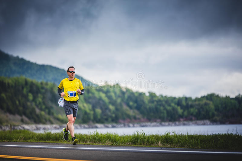 Young Marathoner Alone on the side of the Road and Ocean. CARLETON, CANADA - June 4, 2017. During the 5th Marathon of Carleton in Quebec, Canada. Young stock images