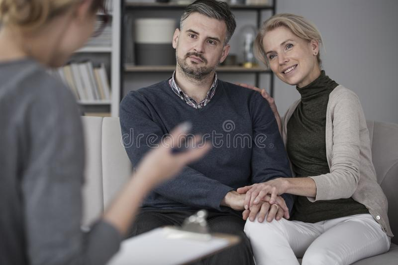 Marriage during marital therapy. Young marriage during marital therapy smiling to their blond therapist in glasses stock photo