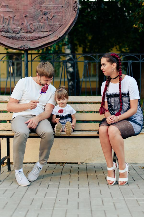Young married couple on bench in park, mother with daughter with lollipop in hands in one-year dresses. 1 stock images