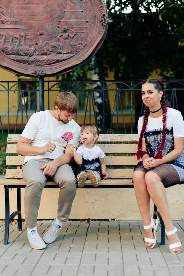 Young married couple on bench in park, mother with daughter with lollipop in hands in one-year dresses. 1 royalty free stock image