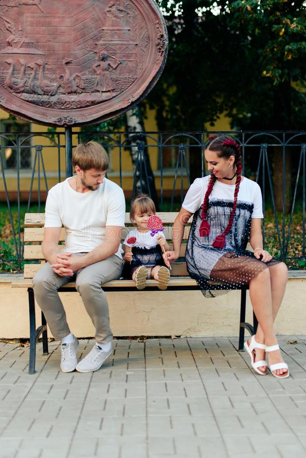 Young married couple on bench in park, mother with daughter with lollipop in hands in one-year dresses. 1 royalty free stock images