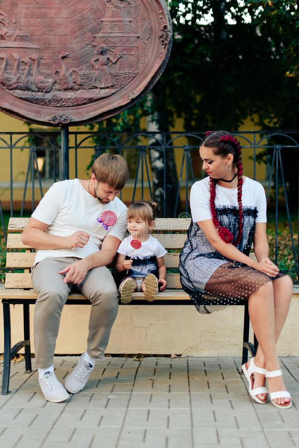 Young married couple on bench in park, mother with daughter with lollipop in hands in one-year dresses. 1 stock photo