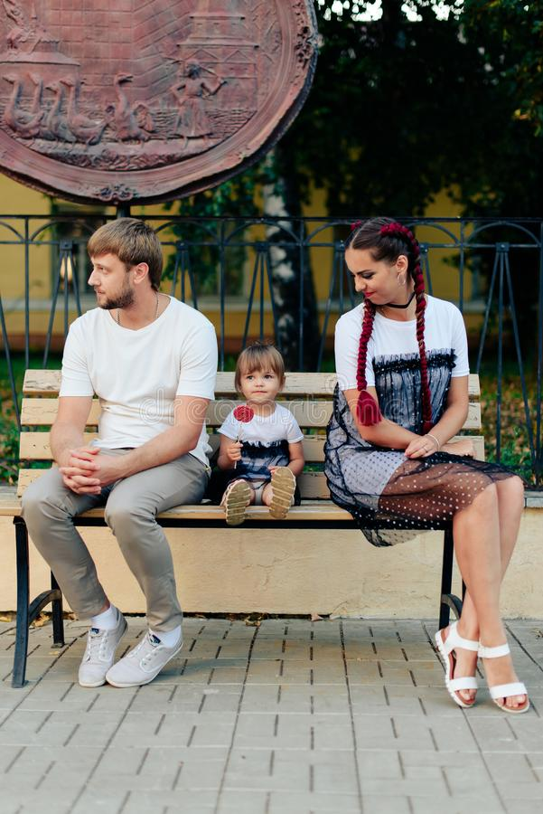 Young married couple on bench in park, mother with daughter with lollipop in hands in one-year dresses. 1 stock image