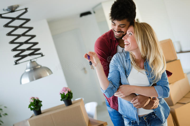 Young married couple with boxes and holding flat keys stock photo