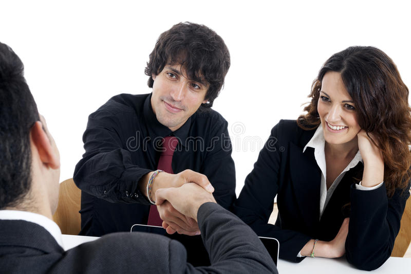 Young married couple at desk in a business meeting. On white stock image