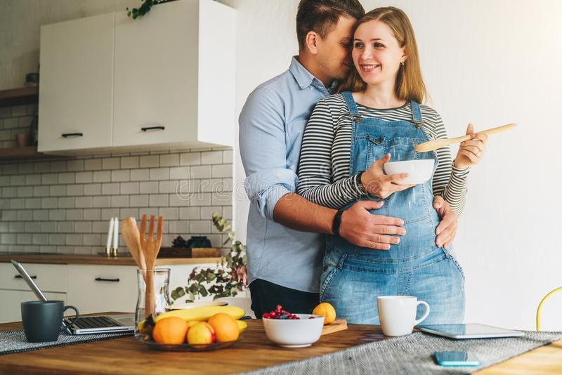 Young married couple embraces standing near table in kitchen. Husband hugs his pregnant wife stock photos