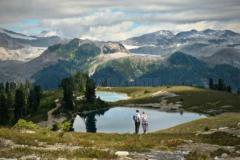 Young married couple hiking in mountains near beautiful alpine lakes and glaciers. stock images