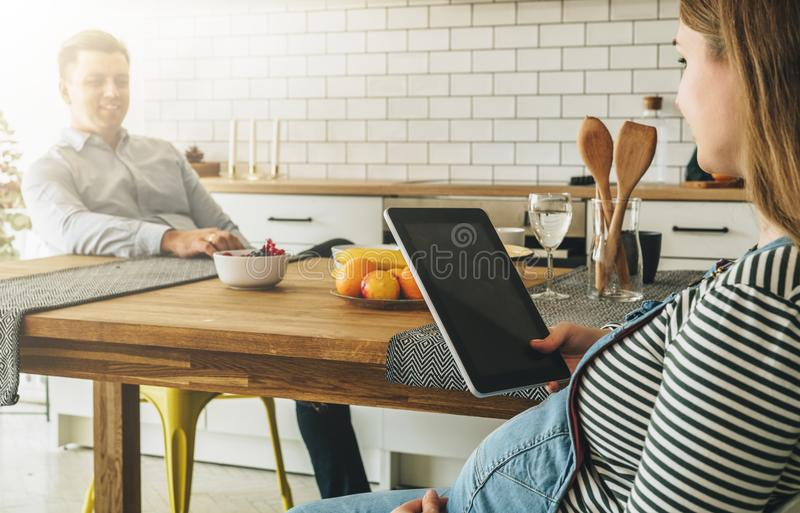 Young married couple in the kitchen. A man sits at a table and with a smile looks at his wife. A pregnant woman sits royalty free stock images