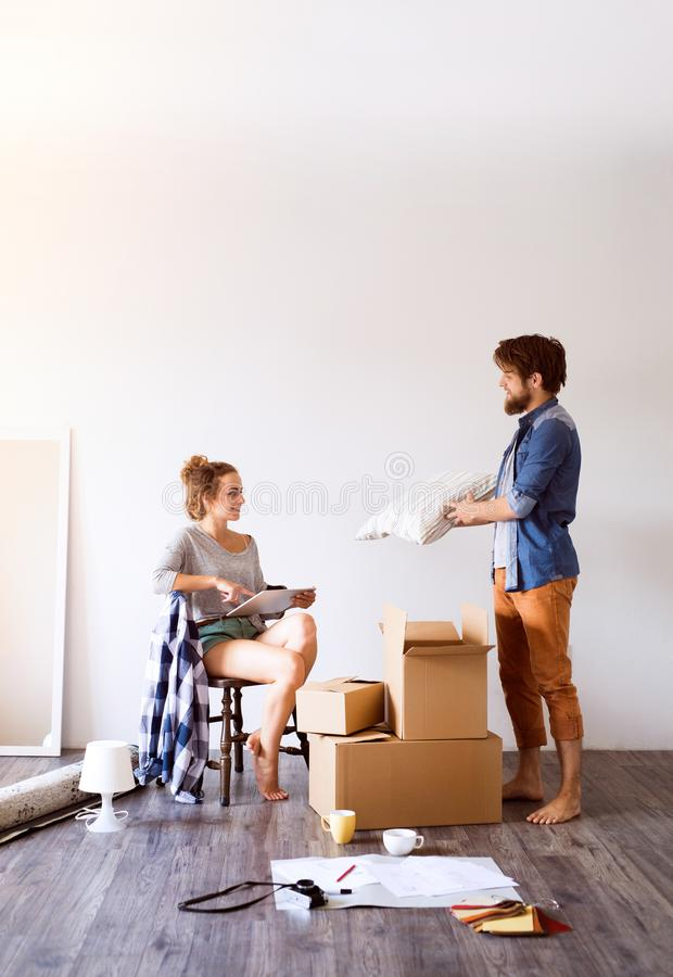 Young couple moving in new house, drinking coffee. stock image
