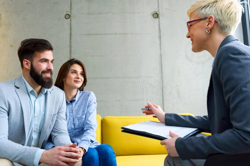 Young married couple with real estate agent. Young married couple at their counselor, their financial advisor or with real estate agent stock photo