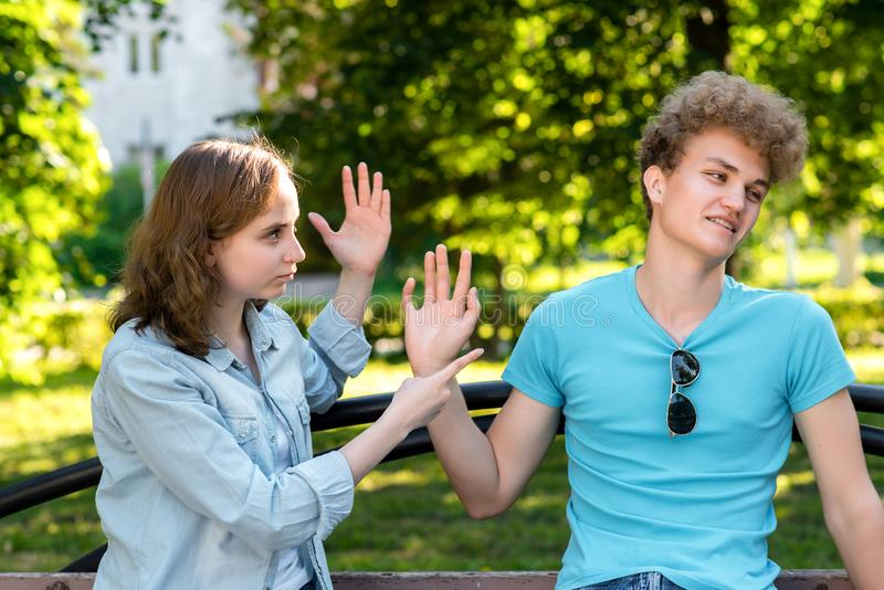 Young married couple. In summer in the park in nature. The girl rebukes the guy. Emotions of mistrust. Insults and stock photo