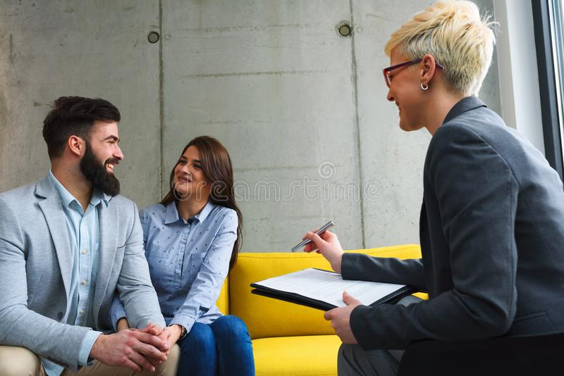 Young married couple with real estate agent. Young married couple at their counselor, their financial advisor or with real estate agent royalty free stock photo