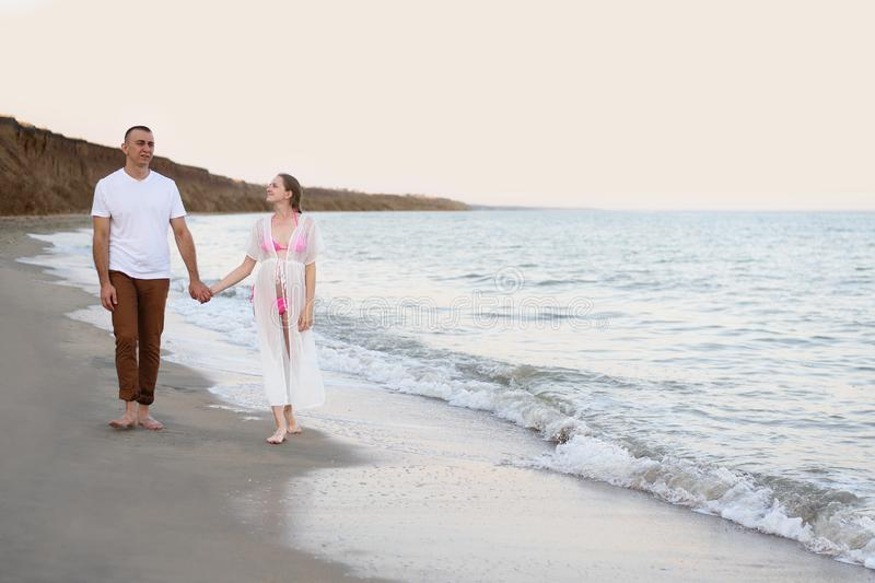 Young married couple walks along the sea coast. Pregnancy. Pre-sunset time royalty free stock images