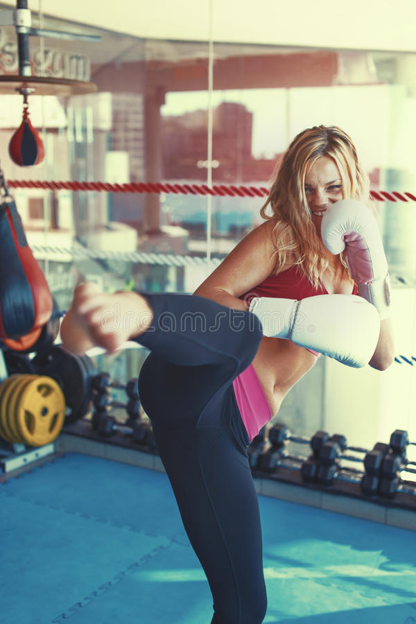 Young martial artist woman kicking in gym into camera graded. Young martial artist woman kicking in gym into camera exercise, color graded royalty free stock image