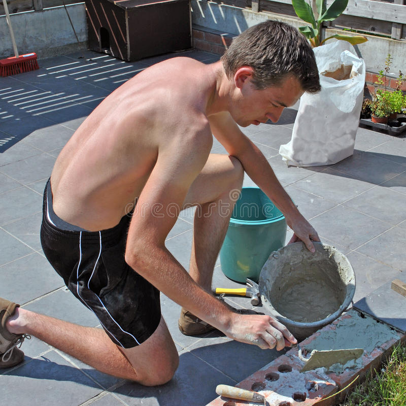 Young mason at work. Garden masonry: young man in naked upperbody putting tiles on a little brick wall stock photos