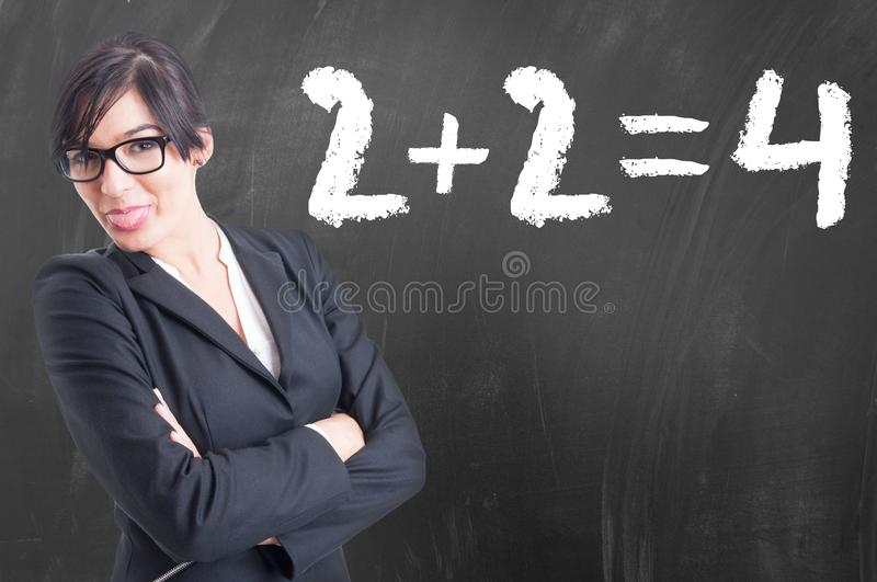 Young math teacher writing numbers on the chalkboard royalty free stock photography