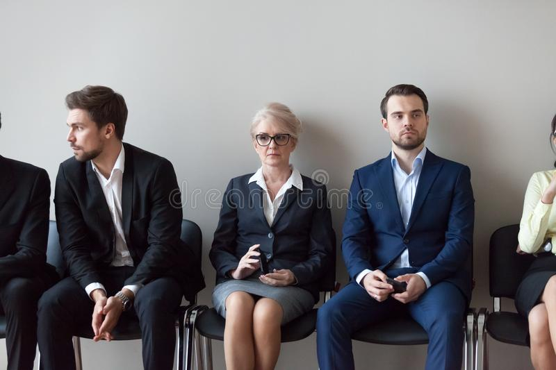 Young and mature candidates waiting for job interview in office royalty free stock photo