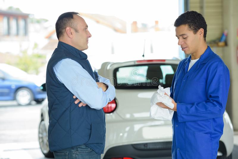 Young mechanic with client in garage royalty free stock images