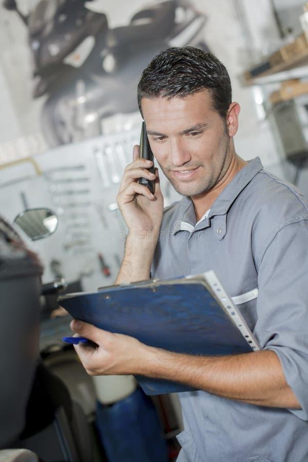 Young mechanic on phone stock image