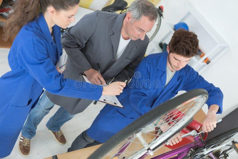 Young mechanic repairing bicycle stock photo