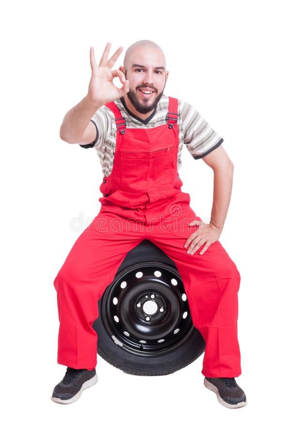Young mechanic showing perfect or good gesture. Isolated on white stock image