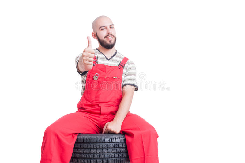 Young mechanic sitting on car wheel and showing like stock images