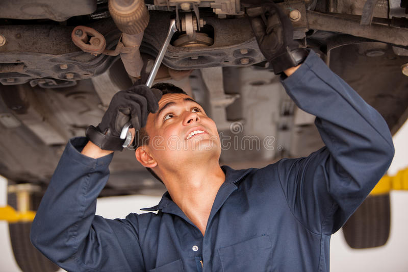 Young mechanic working on a car. Latin young mechanic working on a suspended car at an auto shop royalty free stock photos
