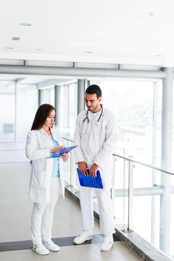 Young Medical Colleagues Analysing Clinical Data On Paperboard stock photo