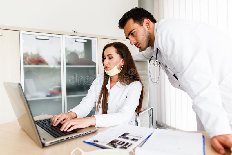 Young Medical Colleagues Working On Laptop royalty free stock images