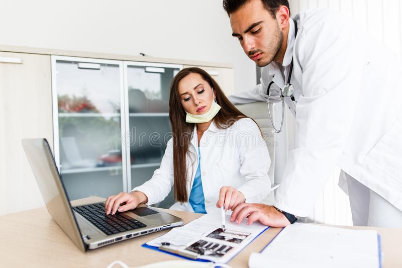 Young Medical Colleagues Working On Laptop royalty free stock photos