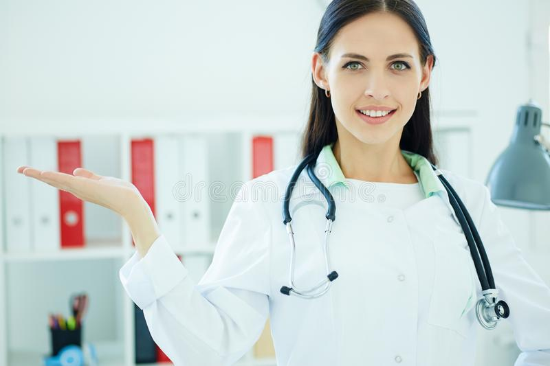 Young female medical doctor presenting and showing copy space for product or text. stock photography