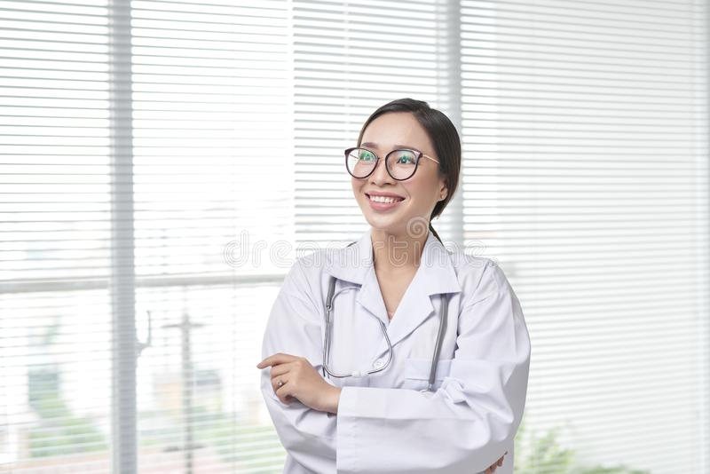 Young medical doctor woman standing on hospital background royalty free stock image