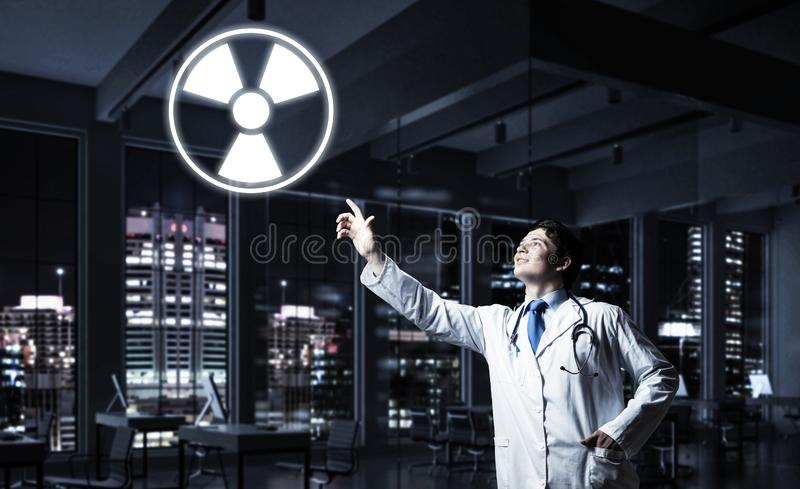 Medical industry and radioactive materials. Young medical industry employee interracting with glowing radioactive symbol while standing against night cityscape stock image