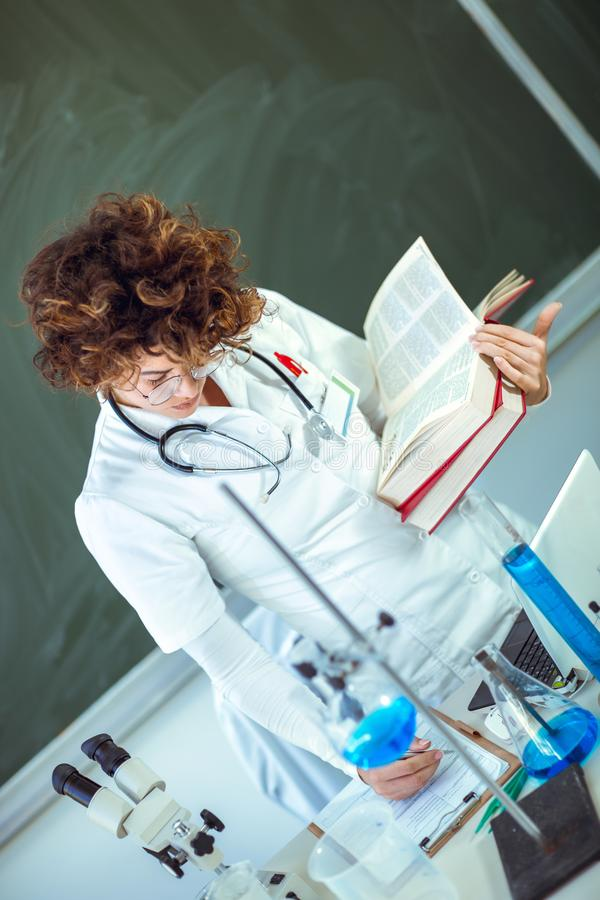 Young medical student learning in laboratory. Young medical student learning and writes in laboratory royalty free stock photo