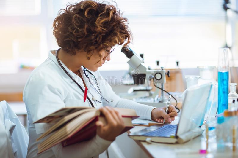 Young medical student learning in laboratory. Young medical student learning and writes in laboratory royalty free stock image