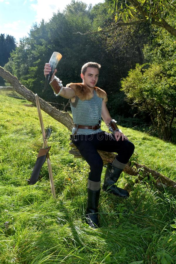 Young Medieval dressed one man, holds drinking horn high in the hand, looks forwards. And sits on branch in the nature , arrow and curve stands besides stock images