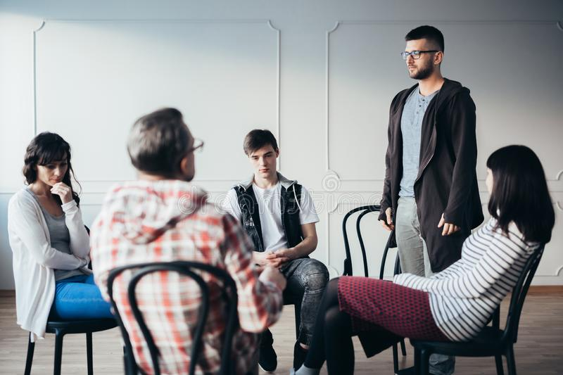 Young man admitting that he is an alcoholic during support group meeting. Young men admitting that he is an alcoholic during support meeting royalty free stock photography