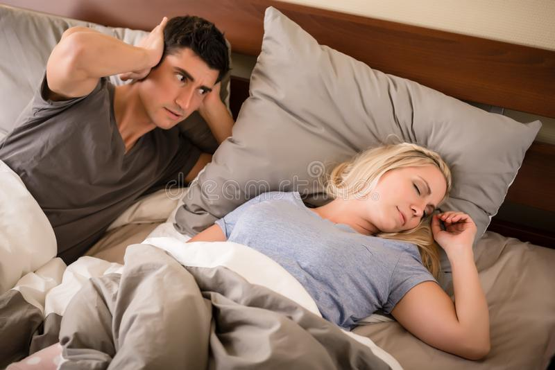 Man annoyed by the snoring of his partner. Young men annoyed by the snoring of his partner sleeping in bed at night stock photos