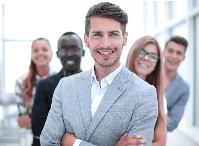 International business people standing with folded arms smiling at the camera. Young men with arms folded and friends behind him against a white background stock photography