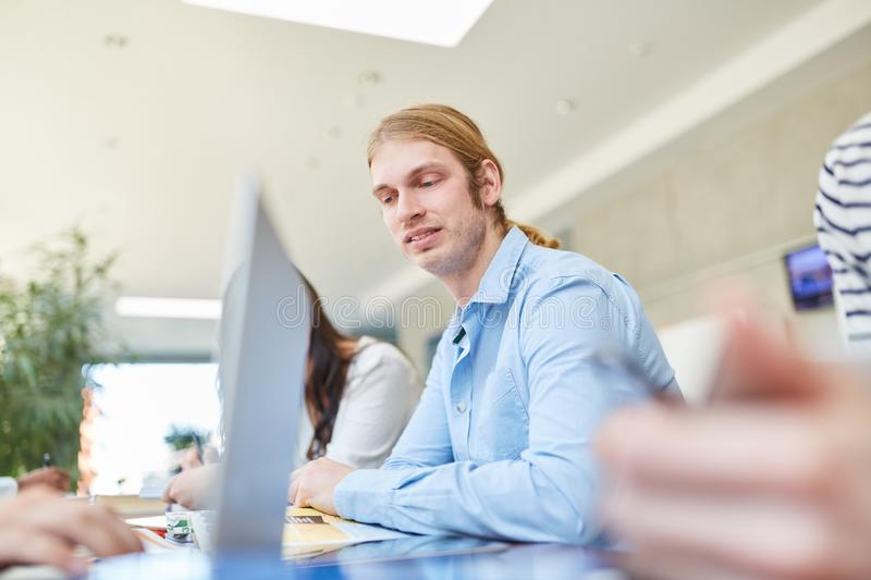 Young man as student in study group stock image