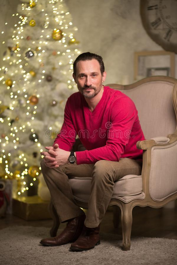 Handsome man in arm chair. Young men with beard sitting in luxury arm chair. looking thoughtful stock photography