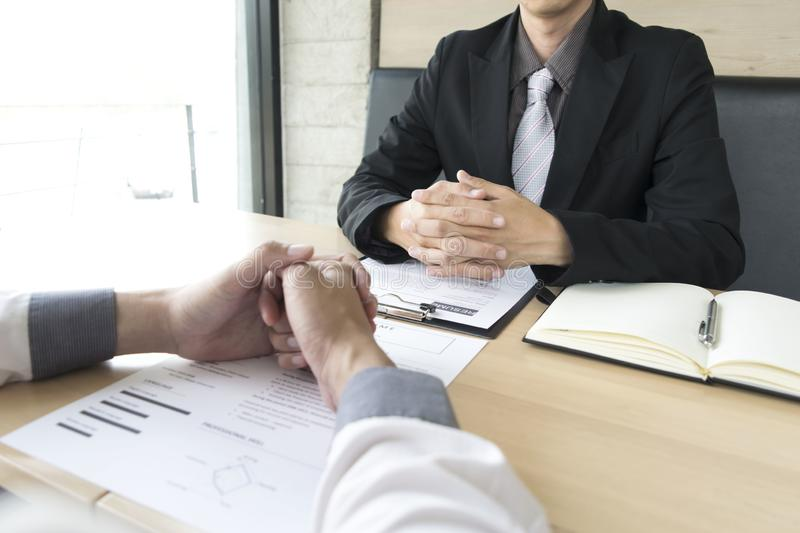 Young men are being interviewed by employers. The employer wears a black suit explaining the job application stock image