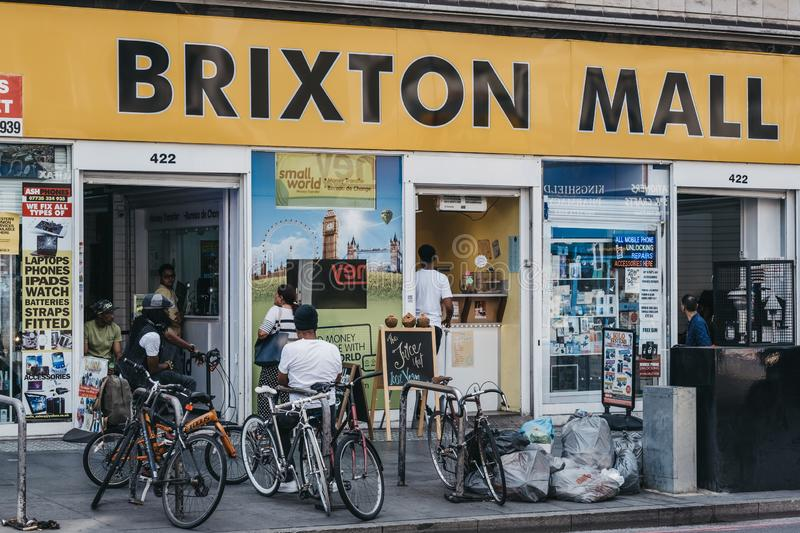 Young men on bikes relaxing outside Brixton Mall. Brixton, South London, UK stock photo