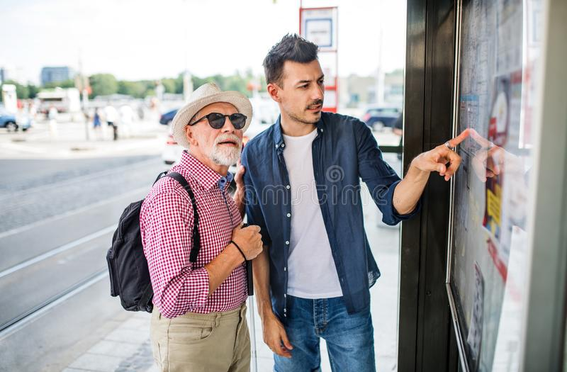 Young man and blind senior with white cane at bus stop in city. royalty free stock images